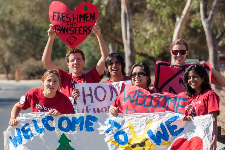 Orientation volunteers hold signs to welcome new students to campus / L.A. Cicero