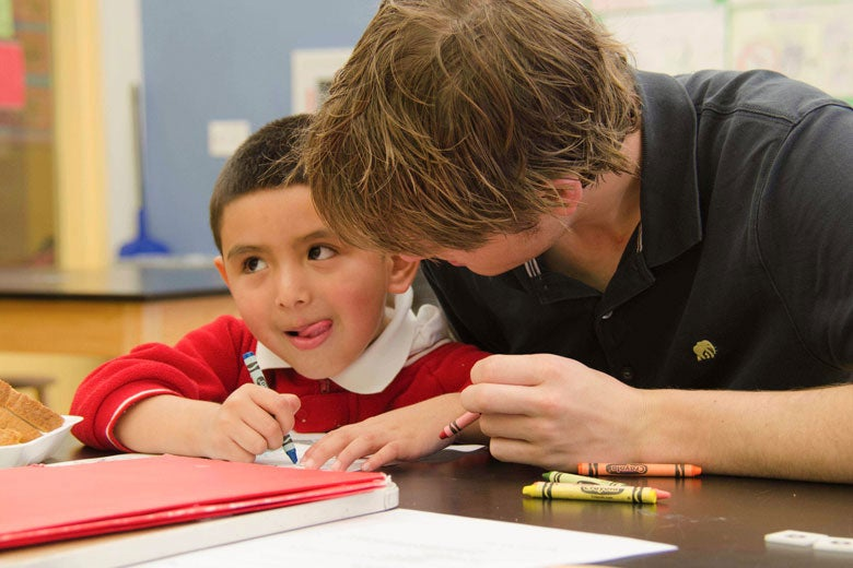Young man helping a small boy with his school work. / Photo: Joy Leighton