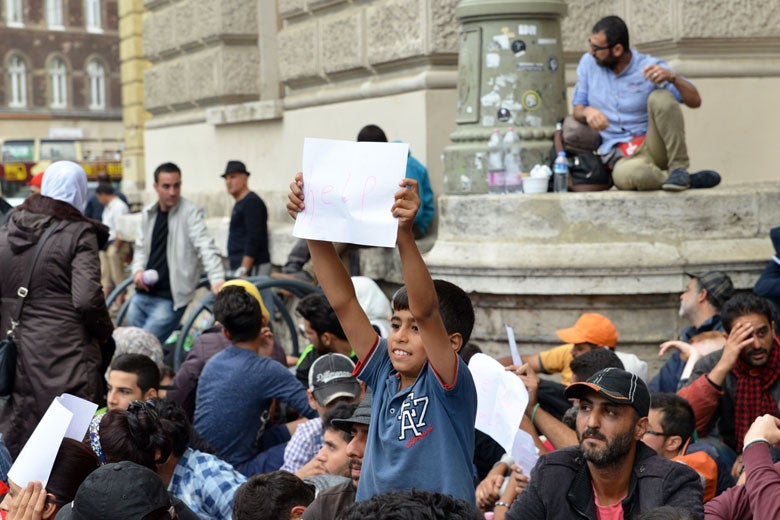 Boy holding a 'help' sign surrounded by many other refugees.