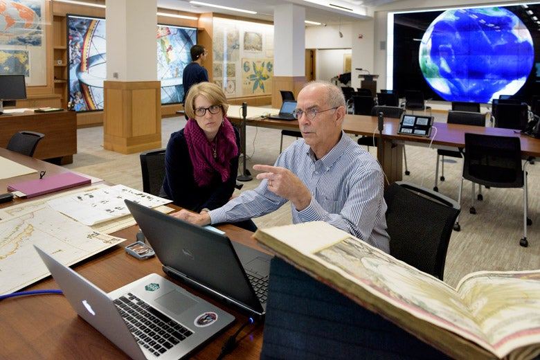 Man and woman sitting in front of a computer with a world map behind them