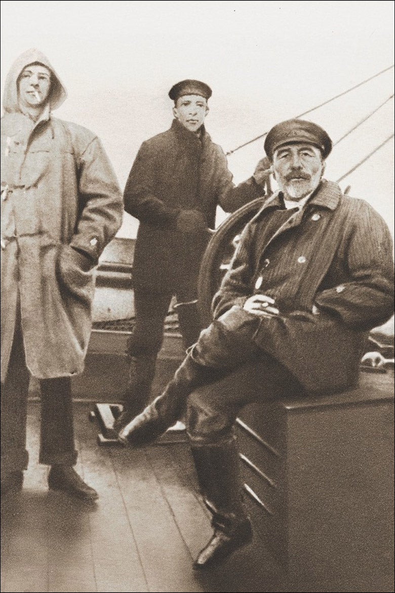 Joseph Conrad seated on deck of a ship with two sailors behind him.