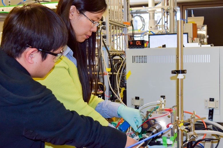 Xiaofei Ye (left) and Liming Zhang adjusting experimental device