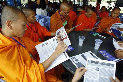 Buddhist monks reading court documents around a table during break in genocide trial in Cambodia / AP Photo/Heng Sinith