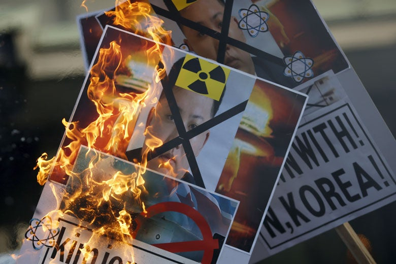 protest signs against Kim Jong-un and nuclear testing