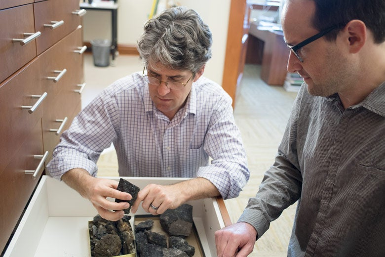 Kevin Boyce and Matt Nelsen handle Carboniferous-era petrified wood fossils
