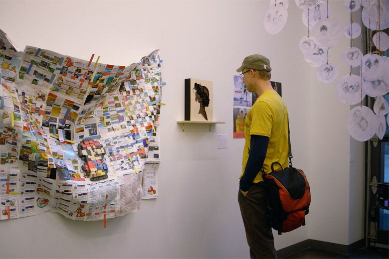 man viewing student art on exhibit / Kurt Hickman
