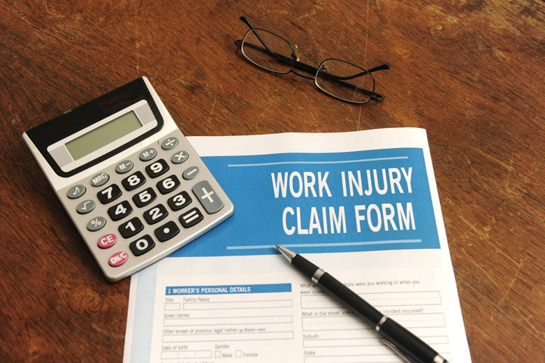 work injury claim form and calculator on desk / mangostock/Shutterstock