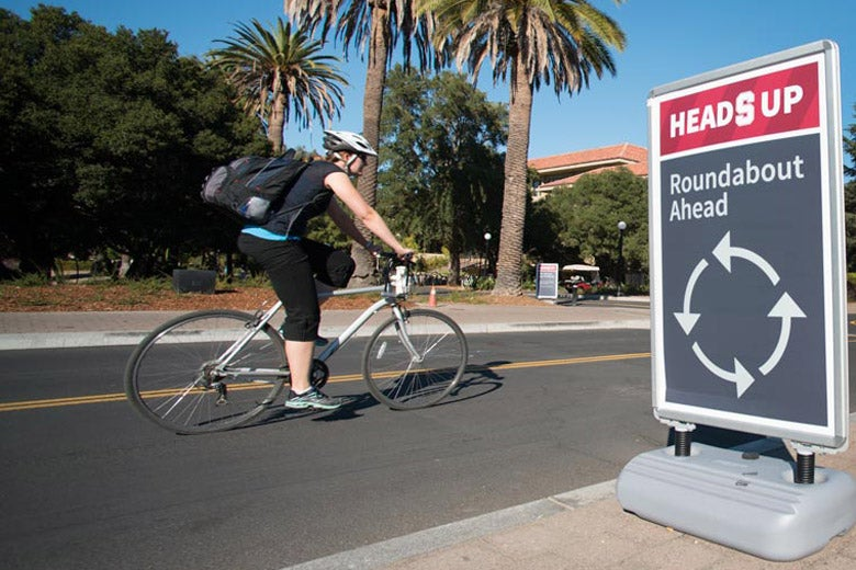 Bicyclist riding in front of a sign indicating roundabout ahead