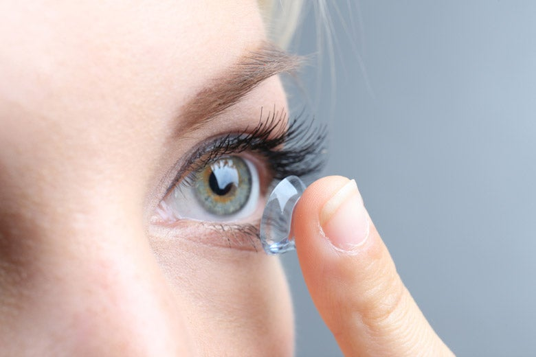 Closeup of woman putting contact lens in her eye