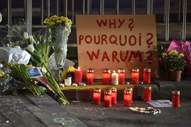 Sign reads 'Why?' in multiple languages at a memorial near Maelbeek metro station in Brussels